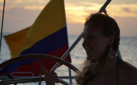 girl on sailboat with colombian flag in background