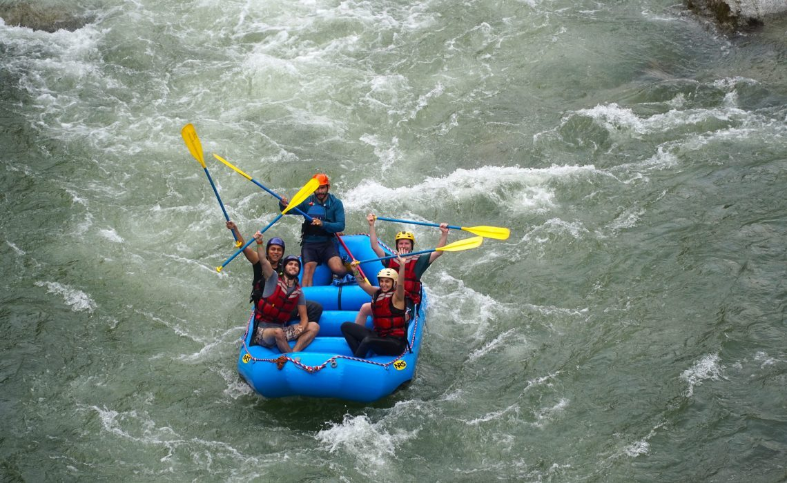 people in raft waving at photograph