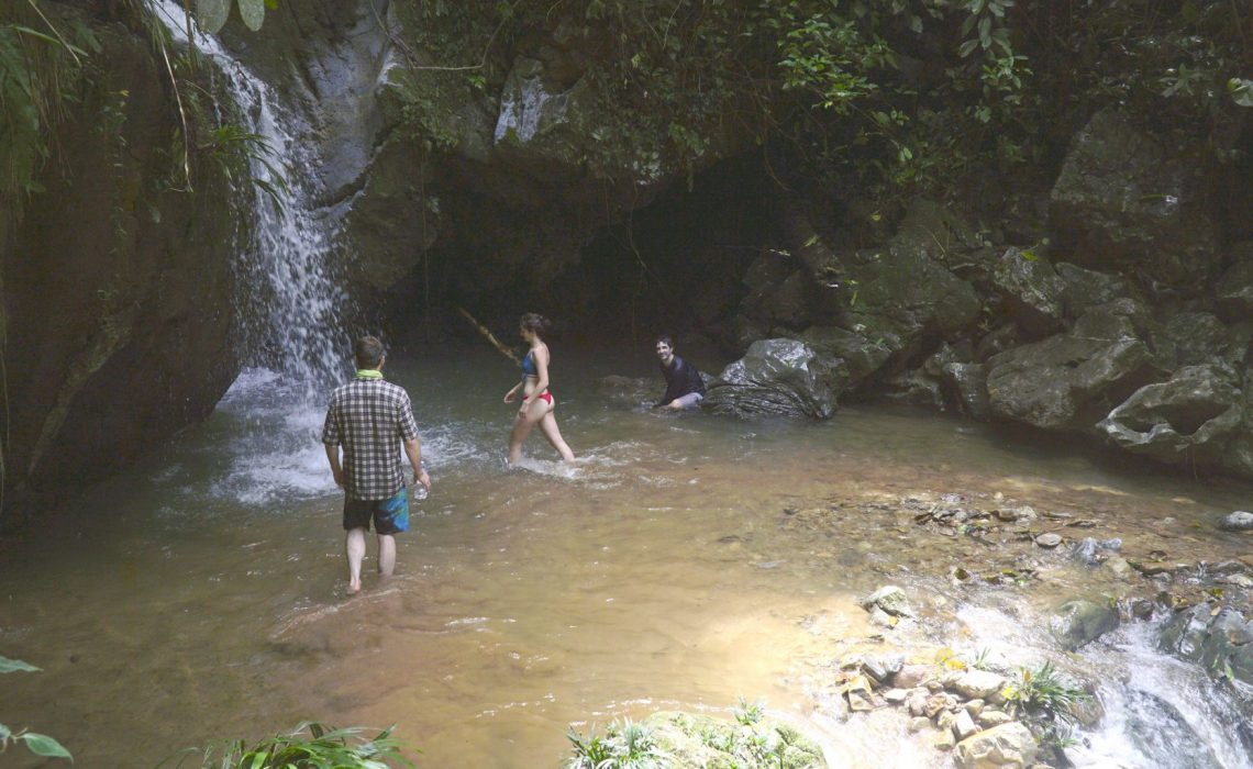 group swimming in waterfall