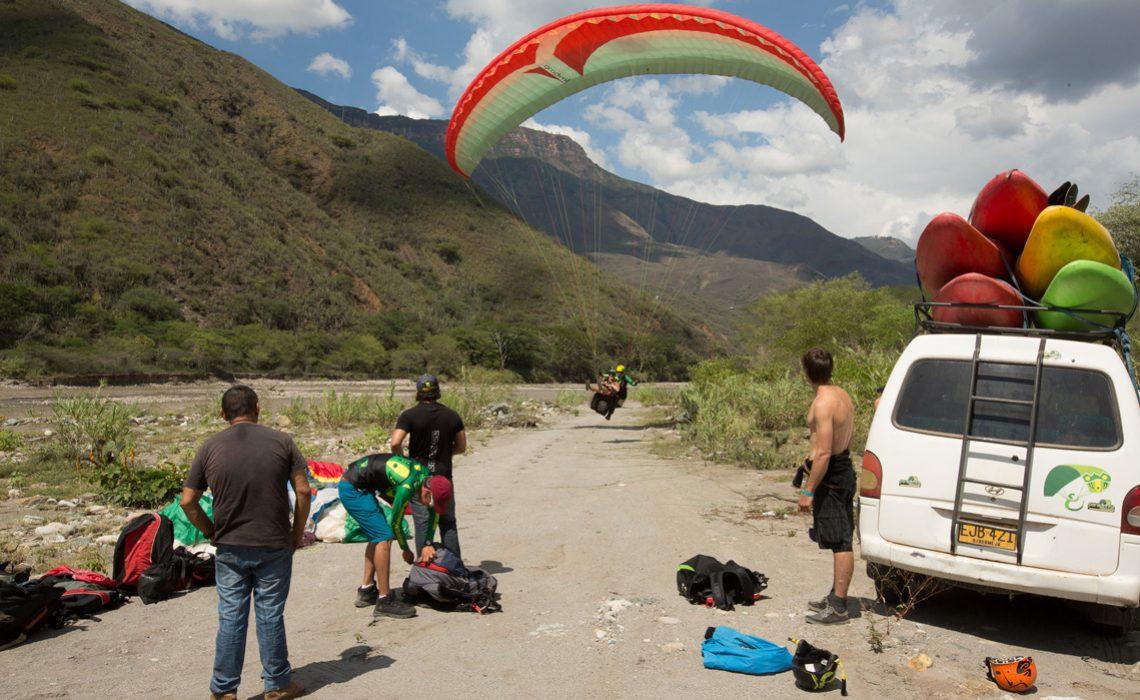 paragliders landing beside van loaded with kayaks